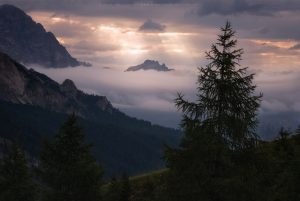 One of the peaks of the Dolomites emerges from morning low cloud as the first rays of light penetrate the cloud