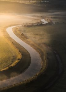 The meandering Cuckmere river in East Sussex at first light as a single swan glides along the water