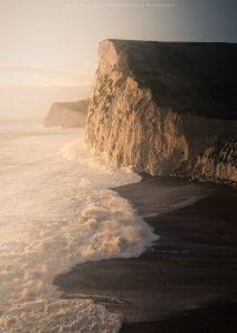 Late afternoon winter light illuminates Bats Head in Dorset at the wind creates a wild tide