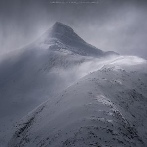 High winds throw spindrift around high up on a Scottish mountain peak