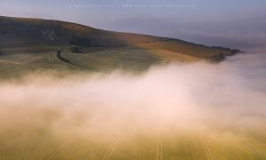 The historic Long Man of Wilmington stands over the rolling mist of an Autumn in Sussex