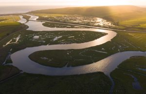 Sun sets on the fascinating meandering sea estuary at Cuckmere Haven, Sussex